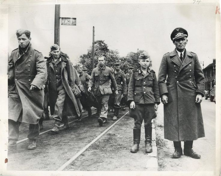 1944- Ten-year-old German boy soldier poses with his Major after their capture in Antwerp, Belgium. Hundreds of other prisoners taken with them march past in background.