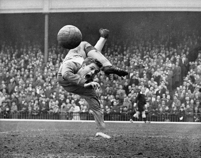 Blackpool goalkeeper Gordon West is rendered agog by his own miraculous save during a match against Arsenal at Highbury, 1961. This photo (taken byRon Bell) won first prize in the 'Sports Pictures in the British Press, Pictures of the Year Competition' in the same year.