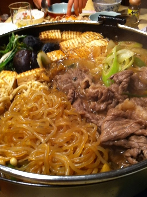Sukiyaki. thin slices of beef cooked with vegetables at the table in soy sauce, sake and sugar.