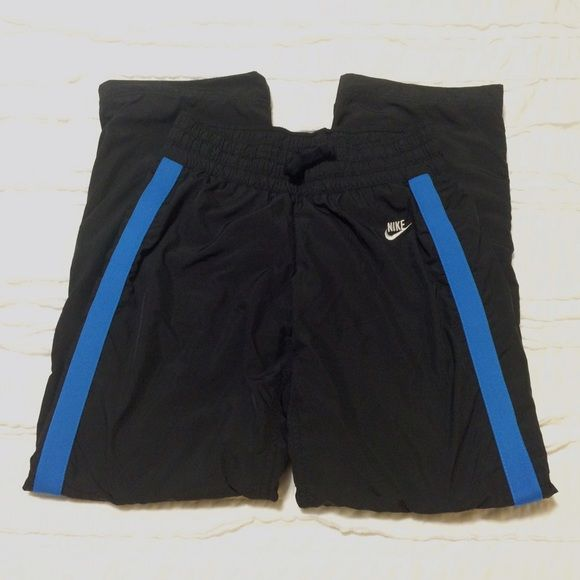 Nike Ladies Workout Pants Black Nike workout pants with blue stripe down each leg and white Nike logo. Snap back pocket, drawstring at waist and a loose comfortable fit. Size XS in Ladies which will fit women's size 0-2 comfortably. Also available in hot pink instead of blue. (See other listing). Nike Pants Track Pants & Joggers