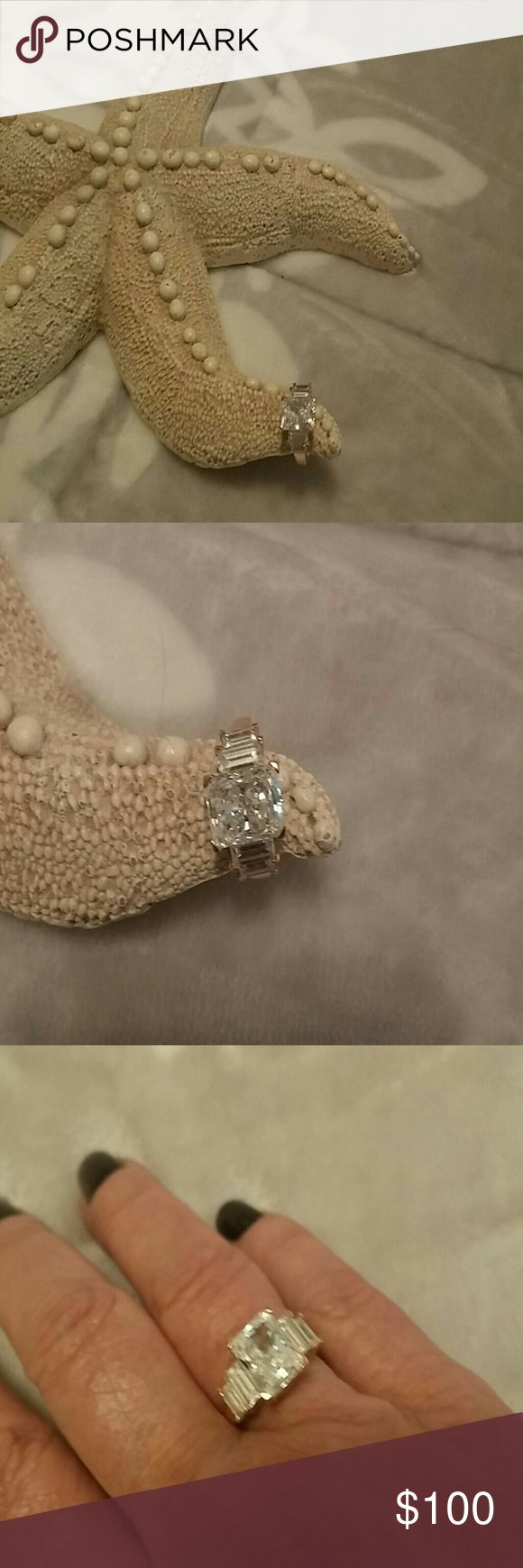 Beautiful CZ ring This is an authentic CZ ring that I ordered for a service anniversary gift. Its over 3 ct. & has just a beautiful shine to them. I have never worn it & was purchased for $300.  The size is either a 7 or 7.5 Im not sure which as it has been years in my jewelry box. No papers. Price is firm, if I dont sell it I will keep it. Jewelry Rings