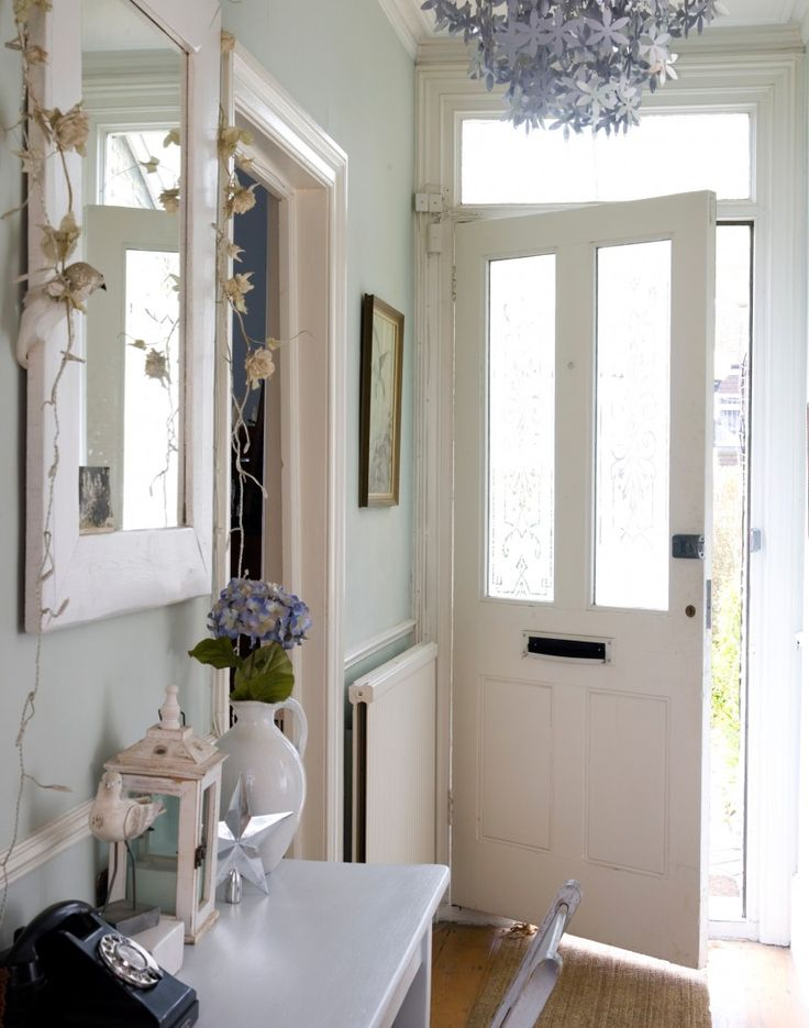 Pale green hallway with silver floral chandelier