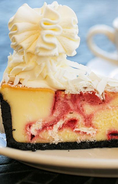 Indulge in this White Chocolate Raspberry Truffle Cheesecake from @ccfactory. Eat in or order online from the comfort of home. #NationalCheesecakeDay