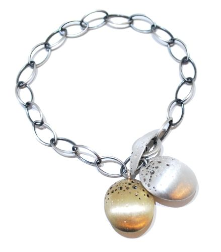 This sterling silver bracelet features silver oval chain that has been lightly oxidised to contrast the gold and satin silver of the pods. The pods and clasp join together to create a feature and resemble berries from a tree. The hollow structures have tiny clustered holes that flood light to the other side creating depth to the design.