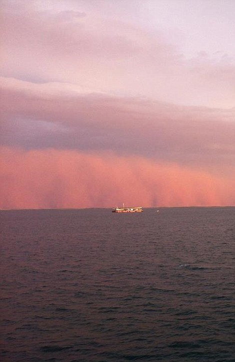 Menacing: The towering red dust storm is pictured rolling across the ocean as it approaches Onslow in West Australia