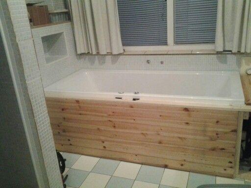 Badkuip is af getimmerd met vuurhoudt in conditie blauw witte tegels