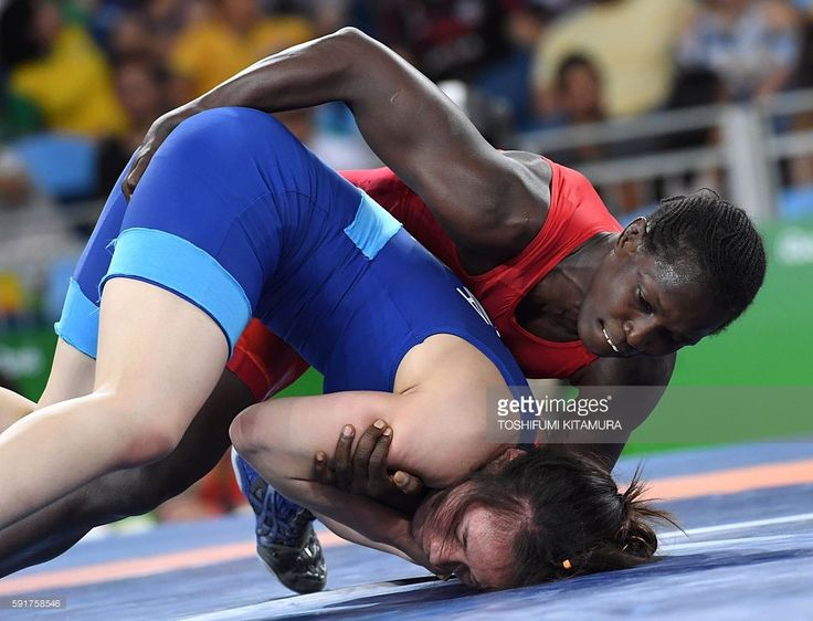 Senegal's Isabelle Sambou (red) wrestles Vietnam's Thi Lua Nguyen (blue) in their women's 53kg qualifying match on August 18, 2016, during the wrestling event of the Rio 2016 Olympic Games at the Carioca Arena 2 in Rio de Janeiro. / AFP / Toshifumi KITAMURA