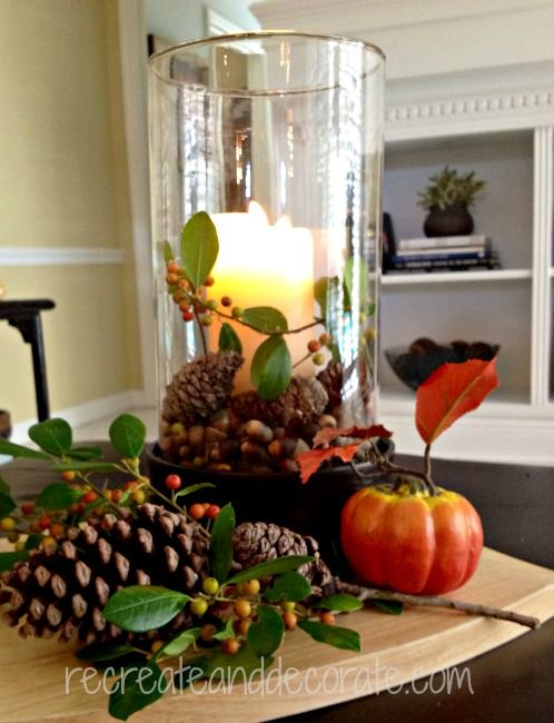 Autumn candle with berries and small pinecones fall