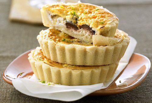Ingrédients pour faire la recette des tartelettes au chèvre : une pâte brisée, une bûche de chèvre, emmental râpé, olives noires, œufs, huile d'olive, thym, sel et poivre.