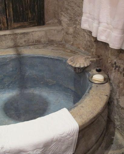 A galvanized tin bathtub set in poured concrete - very spacious and practical!
