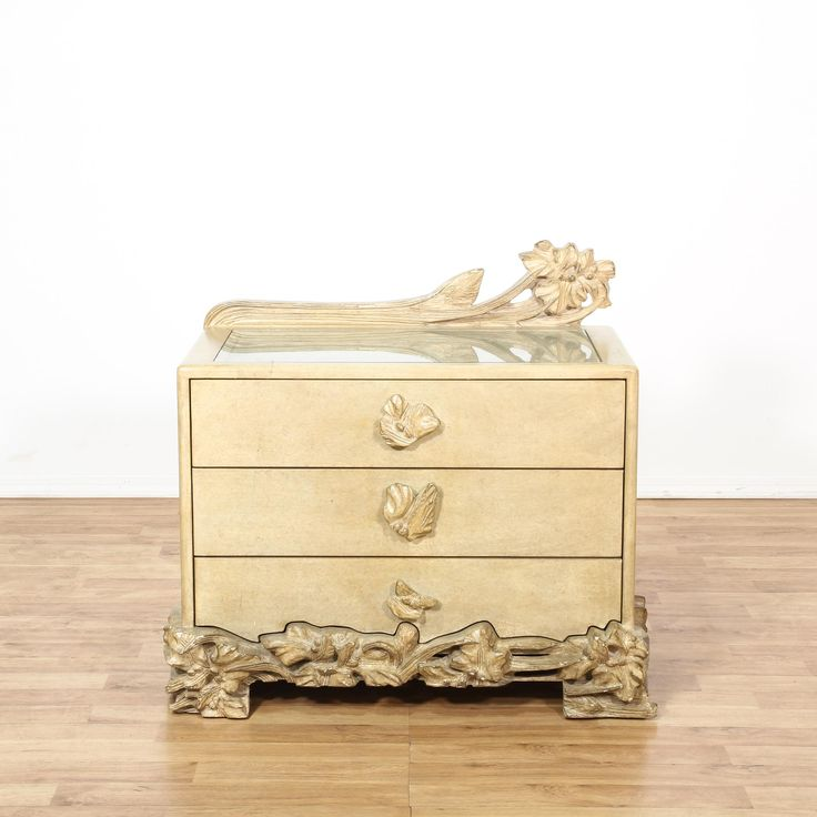 """This """"Phyllis Morris"""" chest of drawers is featured in a solid wood with a light beige finish. This end table dresser has a glass top, 3 drawers and unique intricate carved floral accents. Eye catching piece great for a small bedroom! #americantraditional #tables #tvstand #sandiegovintage #vintagefurniture"""