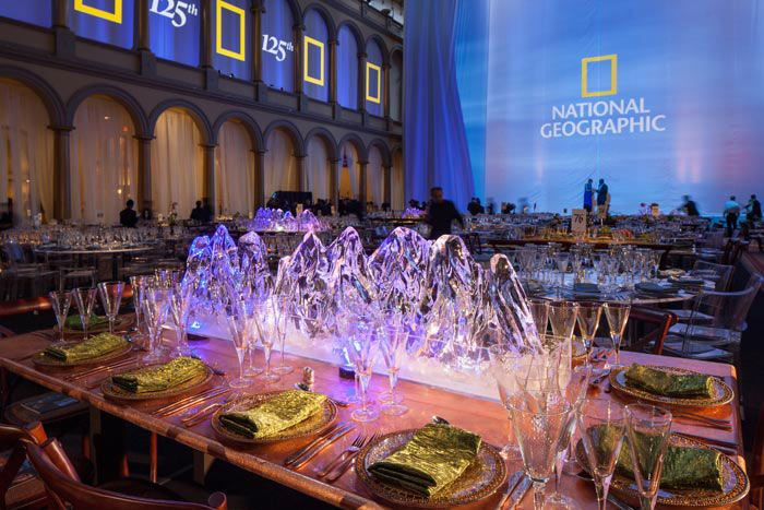 """At the 125th anniversary gala for the National Geographic Society in June, the """"Land, Sea, and Sky"""" theme inspired an array of custom tables and toppers, including glacier ice sculptures. Select Lucite tables were not topped with any decorations, but instead held water and plant life, or natural objects like seashells."""