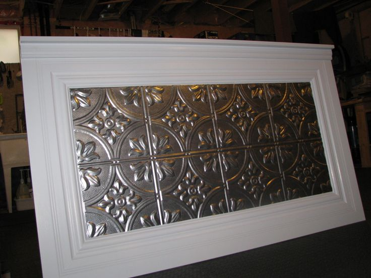 Queen headboard made from house trim and a drop ceiling tile.