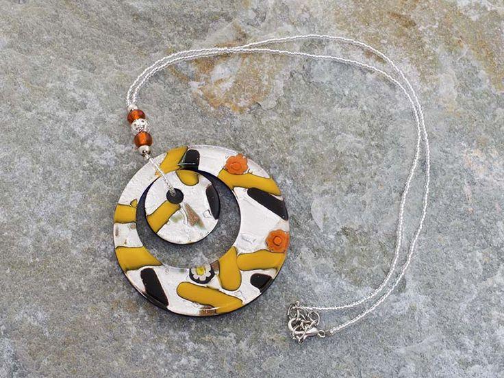 Pendente in vetro di Murano con doppia corona a forma di cerchio dalle variegati sfumature di arancio  La base è di colore bianco con inserti in foglia d'argento e foglia d'oro.  La catena è fatta di perline in conteria, tutto in materiale anallergico (NICKE FREE).  Il cerchio è il simbolo dello spirito e dell'immaterialità dell'anima