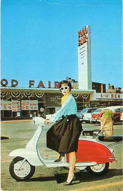 A chic gal on the go sitting on a Lambretta Scooter at a Food Fair supermarket. vintage supermarket  1960s