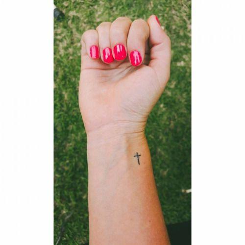 Cross tattoo on Kerrys wrist.