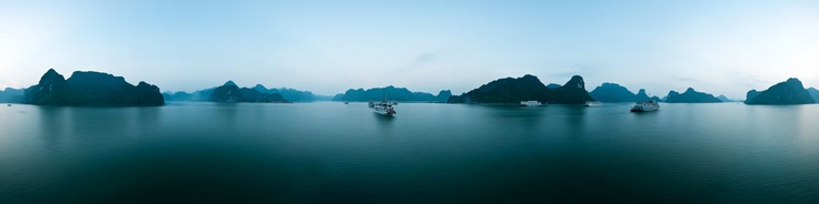 Floating above the waters of Halong Bay right before sunrise. Halong Bay is part of the UNESCO World Heritage and is visited by thousands of tourists each day. Especially the 2 or 3 day cruises are extremely popular since you can sleep on the boat and see Halong Bay in all its glory. This panorama was taken before sunrise on a quiet morning and shows the serene of Halong Bay.