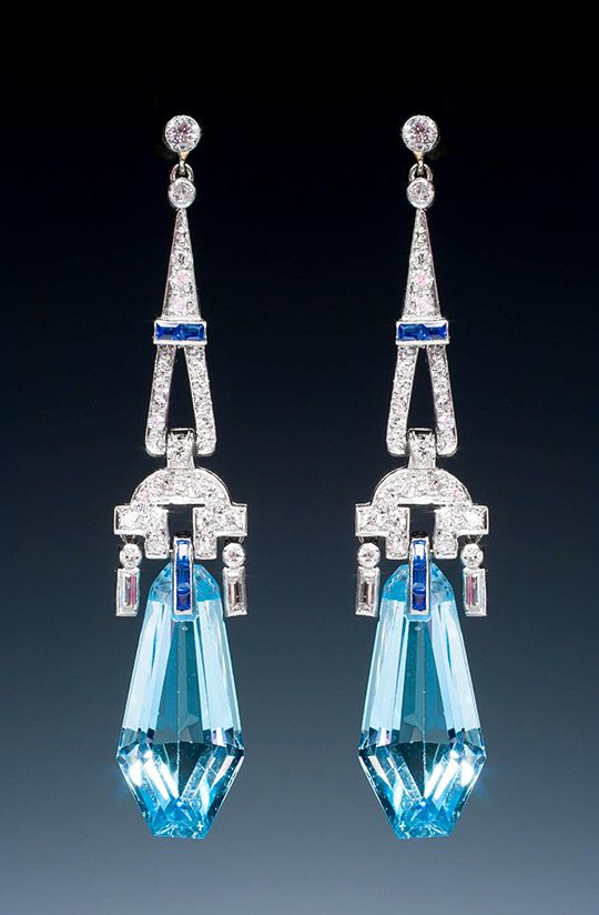 A pretty pair of Art Deco aquamarine and diamond earrings, the kite shaped aquamarines suspend from platinum mounts set with circular cut and baguette cut diamonds and calibré-cut sapphires. In fitted case. English, circa 1925.