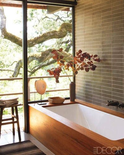 The tile in the master bath is by Heath Ceramics, and the antique stool is English; the enameled-steel tub is fitted with a custom-made teak surround and has oxidized Waterworks fittings. Tour the home here.    - ELLEDecor.com