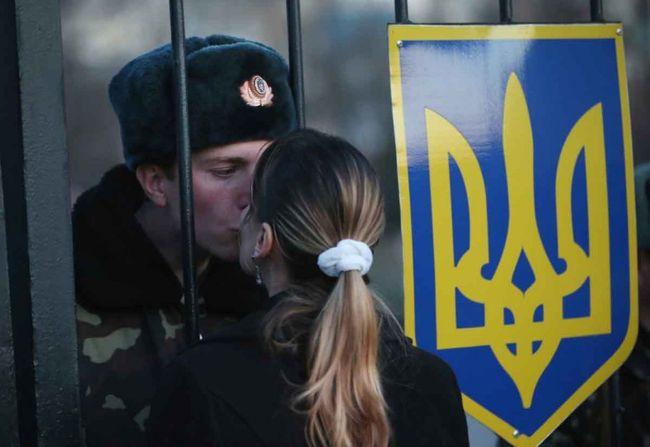 Un soldat ukrainien embrasse sa petite amie à travers un grillage tandis que sa base est entourée par des séparatistes pro-russes.