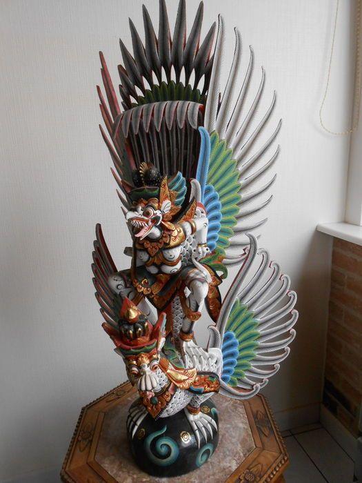 Groot gepolychromeerd Indonesisch beeld 80cm Garuda en Naga - Bali - Indonesië  Een groot formaat gepolychromeerd beeld van Garuda staand op de rug van Naga circa 80 cm hoog afkomstig uit IndonesieIn deze uitvoering zijn zowel Garuda als Naga voorzien van opengewerkte vleugels polychroom beschilderd in mooie passende kleuren zie foto's.Elke vleugel en elk gedeelte is genummerd dit vereenvoudigt het plaatsen van de delenconditie: Het beeld verkeert in een goede conditie één ouderdomsscheur…