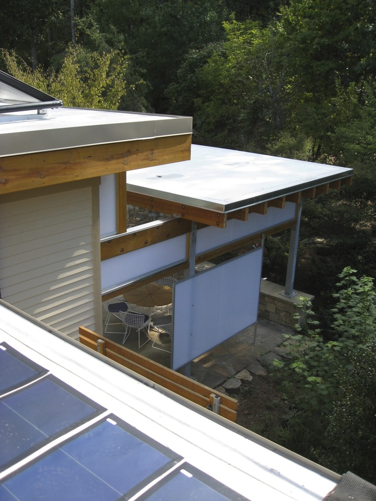A city-country eco farmhouse:  white reflective cool roof, PV paneled, deep overhangs, solar shades, vegetable garden, Chapel Hill, NC, 2010