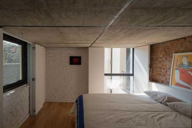 Jemný nádych industriálneho štýlu architekti docielili pomocou pohľadového betónu, ktorý využili ako strop v spodnej spálni aj ako materiál na vytvorenie schodiska.
