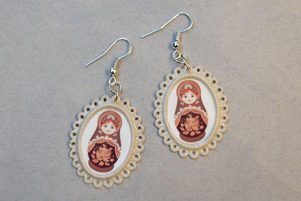 Earrings made of ornate oval-shaped frames and pictures of matryoshka dolls. http://www.minka.fi/korvakorut-kehyskorvakorut-c-36_104.html
