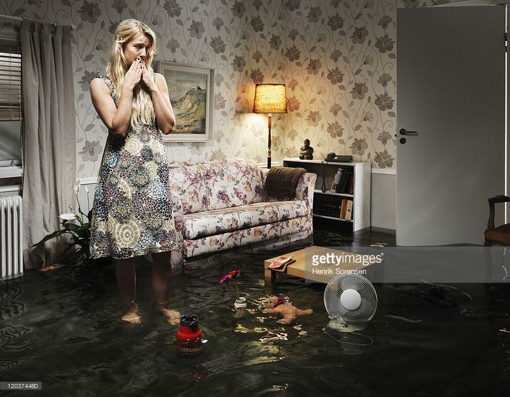 woman in flooded living room, looking at her belongings floating in the water