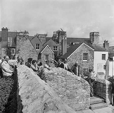 AA087676 A tour group gathered on steps in the foreground, the rear faces of early 17th century merchant's houses along New Street in Plymouth behind