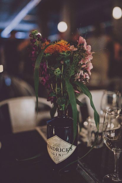 Hendricks Gin Bottles filled with bright flowers as table centrepieces - Images by Ten 21 Photography - Charlie Brear Satin Gown for an Industrial, Urban  City Wedding in Belfast with Bright Florals & DIY decor. Groom wears Designer Hugo Boss Suit & Bridesmaid Wear HighStreet ASOS Dresses.