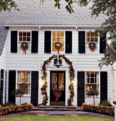 Black shutters on a White House with Christmas decor