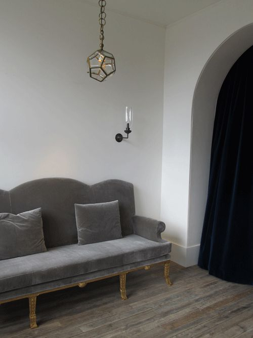 Rose Uniacke. The 'Dodecahendron Pendant Lantern' designed by Adolf Loos (1870-1933) hangs above an elegant antique sofa upholstered in grey velvet. Also visible is a 'Right-angled wall light' designed by Rose Uniacke, available in four different metal finishes, and with clear or frosted glass.