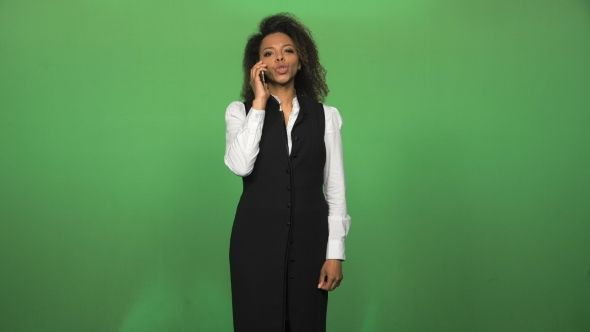 Young African Woman Answering Phone Call by FrameStock Young african business woman in formal suit answering and talking phone isolated on green background. Then turn to camera looking and smile More tags female, successful, talking phone, business, worker, communication, suit, lifestyle, green screen, businesswoman, connection, phone, african, black, turn, looking camera, smile, beautiful, pretty, et