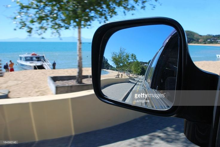 Looking at the view from a car mirror. The scenery surrounding is Kaiteriteri Beach in the Abel Tasman National Park, New Zealand in blur. Selective focus is on the view in the reflection.