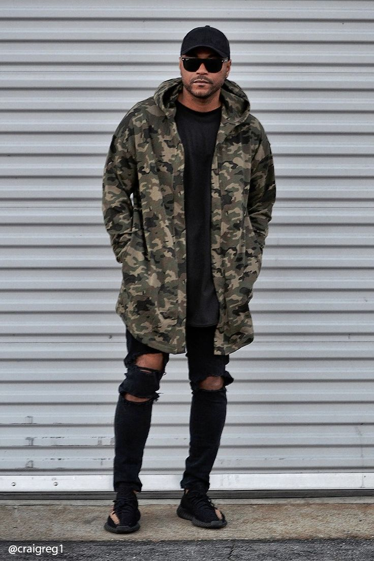 A longline French terry knit hooded cardigan featuring an allover camo print, open front, slanted front pockets, and long dropped sleeves.