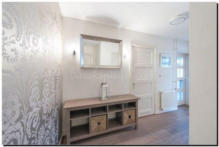 Moderne spiegel in de hal boven een dressoir. Mooi met de zilveren kleuren.