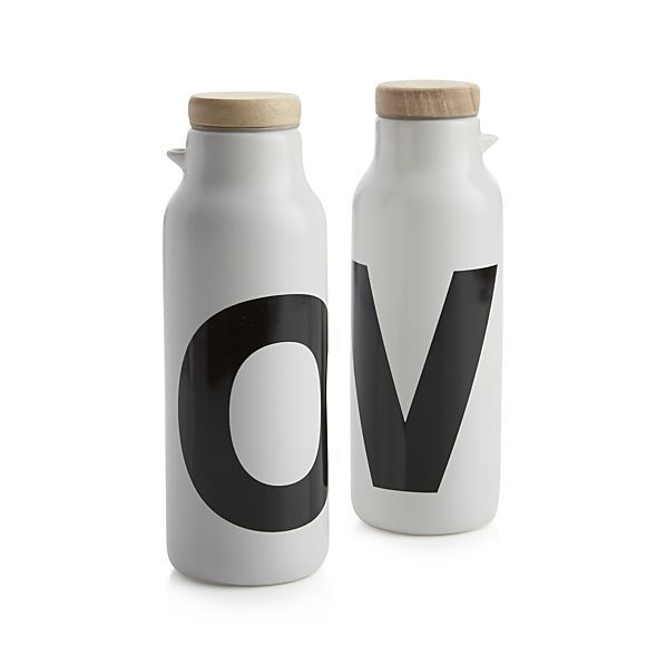 Simply modern bottle set spells out its contents in a black and white letters, rendered in a bold, contemporary font on white stoneware with wooden lids.