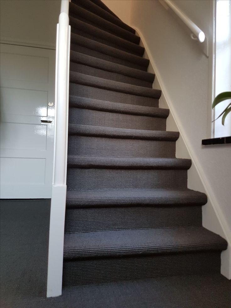 Een trap en hal bedekt met donker sisal tapijt.