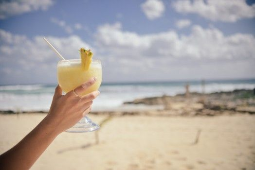 Woman holding cocktail drink on beach