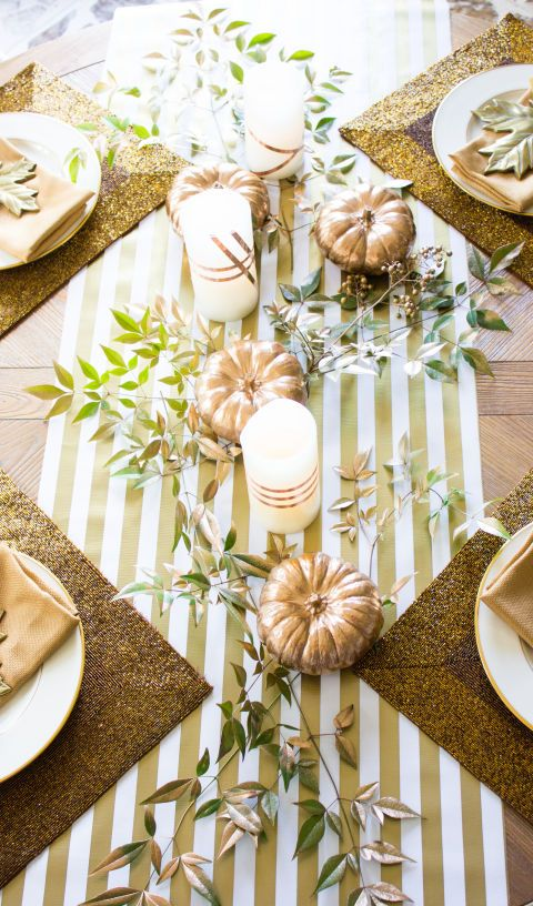 This sparkling DIY table decor features copper-tinted candles created by wrapping copper foil tape around flameless, battery-operated LED candles. Pair the candles with greenery covered in a light coat of copper spray paint and a striped table runner, and you have Thanksgiving decor that illuminates the holiday with a playful glow.
