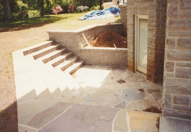Basement entrance steps leading down to a small slat patio for Basement entry ideas