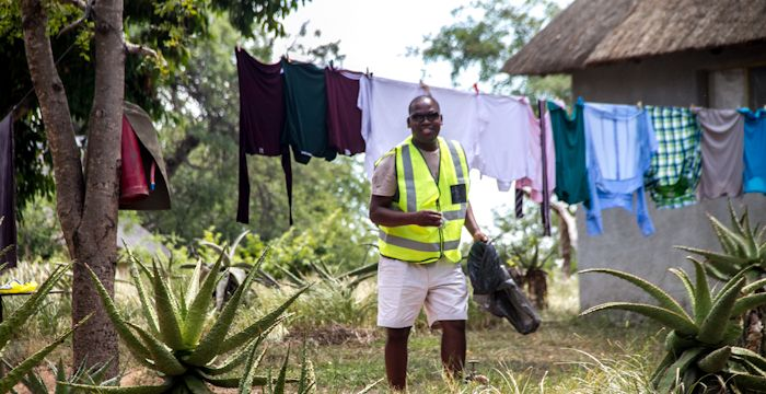 Ranger, Andrea Sithole, stops outside a hut in the village to pick up an old chocolate wrapper. Off camera, to the right, the occupant of the hut asks Andrea if he wants to get the washing off the line while he's there. His grin says it all! Photograph by Ryan James