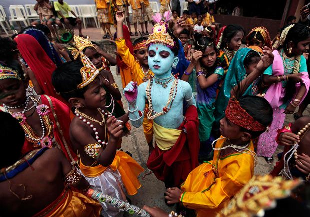 Children dressed as Hindu God Krishna look on during festivities to mark Janmashtami at a school in Mumbai