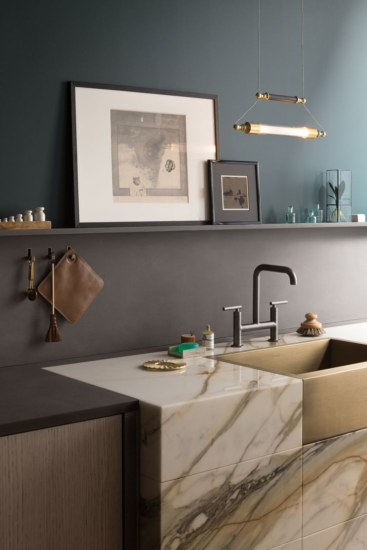 The marble panels have been carefully matched. (In Remodeling 101, learn The Difference Between Calacatta, Carrara, and Statuary Marble.) The bridge faucet is the Kohler Purist in matte black.
