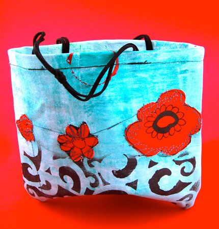 Funky hand painted aqua blue canvas bag with red fabric flowers, black print detail and hand embroidery.