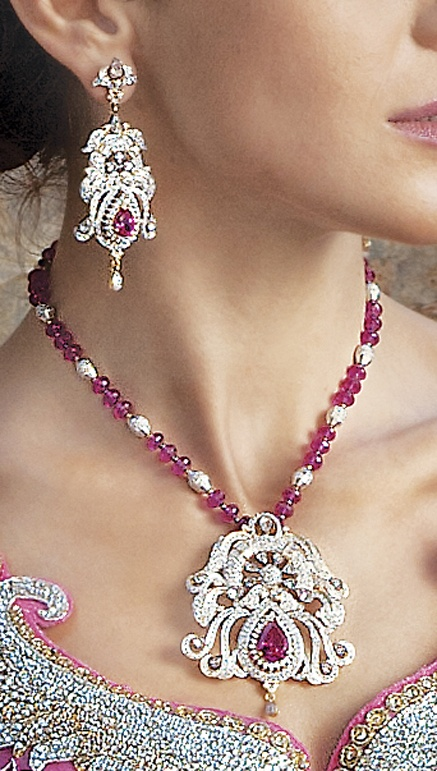 Necklace and earrings in gold and silver polish with cubic zircon and ruby pink stone attached with ruby pink crystal mala by Benzer priced at $219. Buy online at www.benzerworld.com