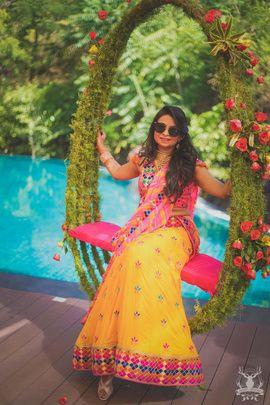 Mehendi Outfit - Abhinav & Deepal wedding story | WedMeGood | Yellow and Pink Lehenga Bride sitting on a Floral and Green Swing #wedmegood #Indianbride #indianwedding #bridal #swing #floral #mehendioutfit #mehandioutfit