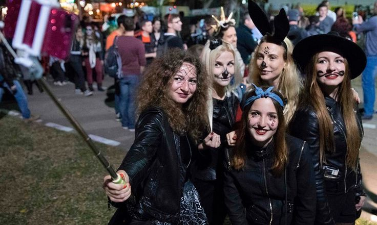 People wearing costumes and facepaint pose as they take part in a zombie walk in Tel Aviv as part of the Purim festival
