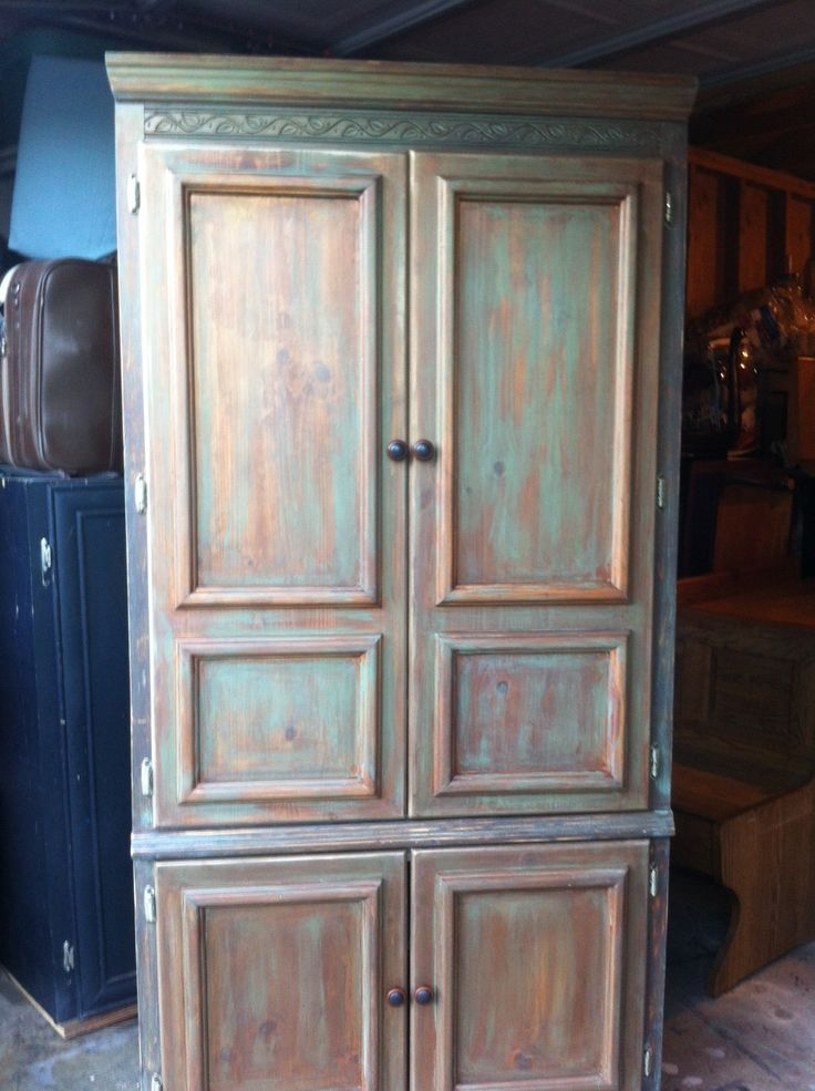 Tall entertainment center, colors are sea green brown tan washed and waxed on top of color..